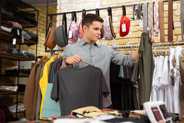 Wybieranie. spokojny, zamyślony młody człowiek, patrząc na koszulki, będąc w sklepie z modną odzieżą i wybierając między nimi