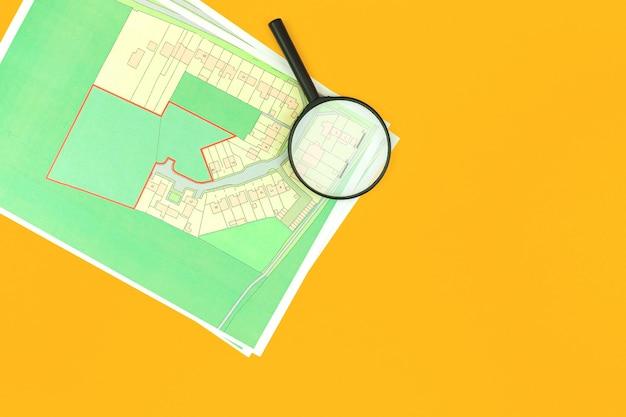 Wybierz działkę budowlaną pod budowę domu, biuro nieruchomości z mapą i tłem ze szkła powiększającego, zdjęcie w widoku z góry
