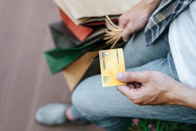 Wybierz ostrość karty kredytowej w ręku młody przystojny mężczyzna w masce, trzymając papierową torbę