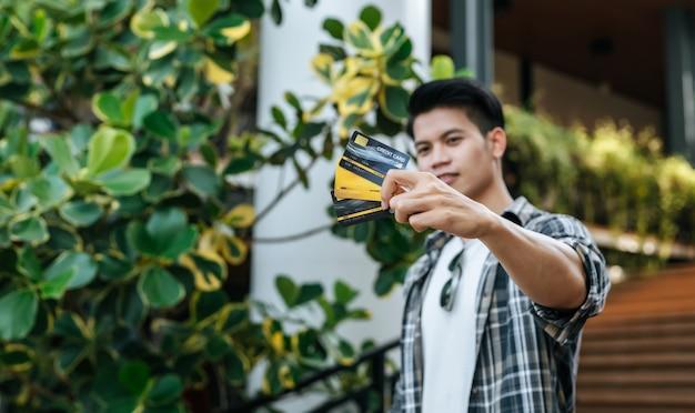 Wybierz ostrość karty kredytowej w ręku młody przystojny mężczyzna w okularach przeciwsłonecznych, trzymając papierową torbę