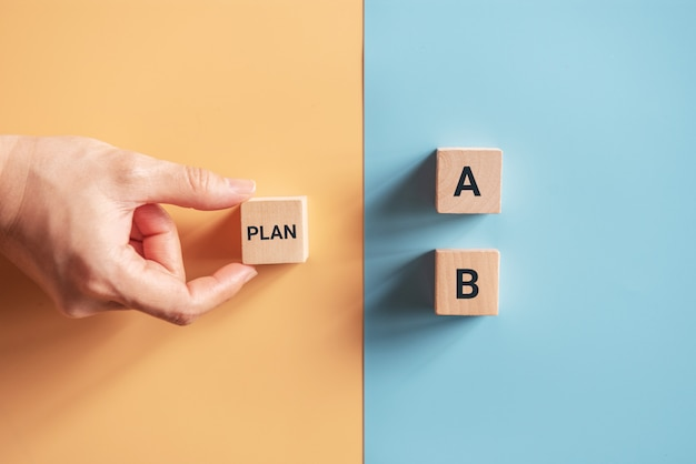 Wybierz ręcznie drewniany sześcian ze słowem plan a do plan b na niebieskim i żółtym tle. pomysł na biznes.