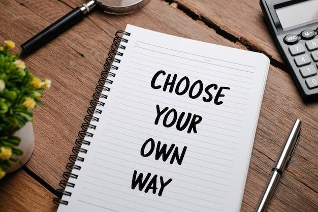 Wybierz swój własny sposób, tekst typografii słów napisany na książce na tle drewnianych, inspirująca koncepcja motywacyjna do życia i biznesu