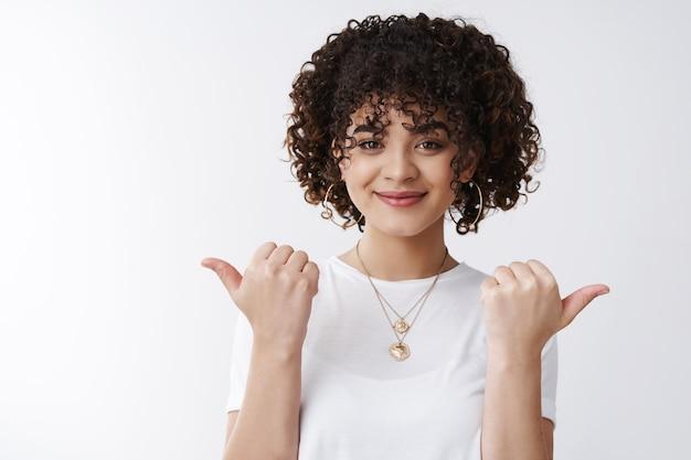 Wybierz swoją drogę. przyjazna, asertywna, stylowa kobieta z kręconymi włosami, wskazująca kciukami w lewo w prawo na boki, dająca warianty promujące produkt, uśmiechnięta, zadowolona, znaleziona idealne miejsca klient