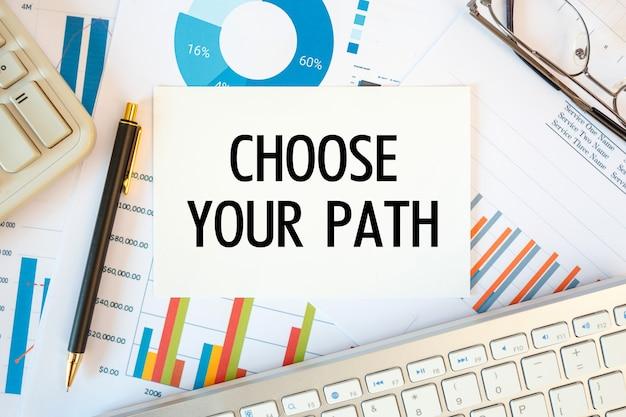 Wybierz swoją ścieżkę znajduje się w dokumencie na biurku z akcesoriami biurowymi, schematem i klawiaturą