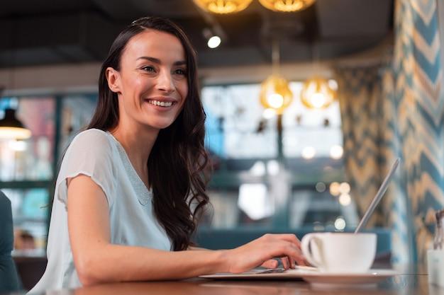 Wybierz swoje miejsce pracy. zadowolony wesoły freelancer pracujący na laptopie, uśmiechając się i siedząc na niewyraźnym tle
