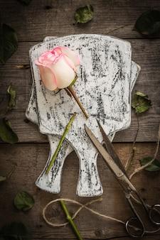 Wyblakła różowa róża na ciemnym rustykalnym