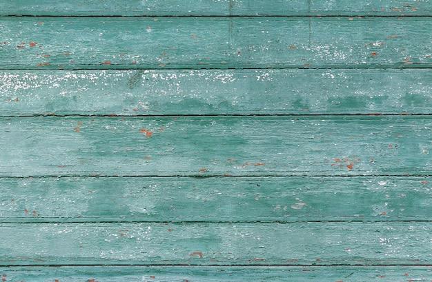 Wyblakłe drewniane deski z popękaną niebieską farbą. stare malowane drewniane deski jako tło.