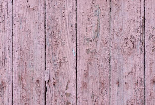 Wyblakłe drewniane deski z popękaną różową farbą. stare malowane drewniane deski jako tło.