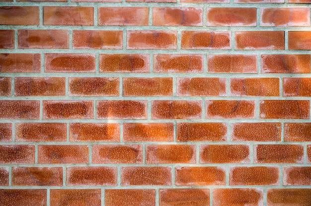 Wyblakły pomarańczowy blok cegieł na ścianie cementu. tło w stylu vintage i retro