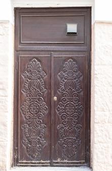 Wyblakły stare drewniane drzwi z rzeźbionymi ornamentami na starym mieście detal zewnętrzny