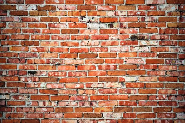 Wyblakły tekstury ciemnobrązowym i czerwonym tle ściany z cegły