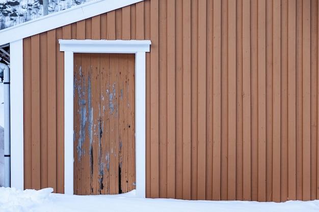 Wyblakły żółty drewniany mur z drzwiami próchnicy w zimie