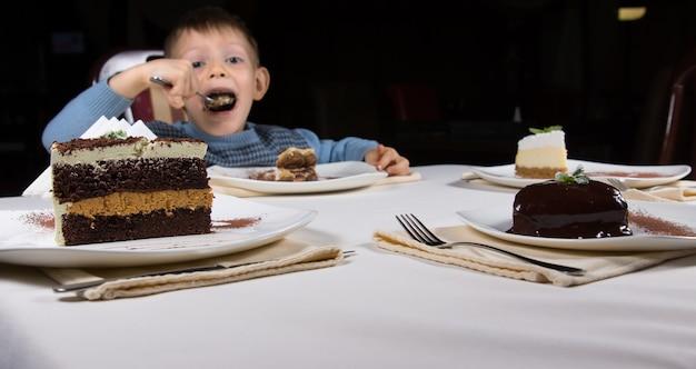 Wybór ciastek czekoladowych na deser z dwoma plastrami, jeden warstwowy ze śmietaną, a drugi glazurowany bogatym lukrem kakaowym, z małym chłopcem jedzącym ciasto za