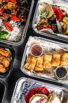 Wybór jedzenia na wynos. sajgonki, pierogi, gyoza i deser w pudełku na lunch. weź i idź żywności ekologicznej. tradycyjne potrawy tajskie i azjatyckie. .