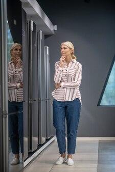 Wybór. kobieta w pasiastej koszuli wybiera lodówkę w salonie i wygląda miło