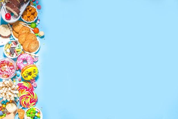 Wybór kolorowych słodyczy. zbiór różnych cukierków, czekoladek, pączków, ciasteczek, lizaków, widok z góry lody na modnym jasnym niebieskim tle słonecznym