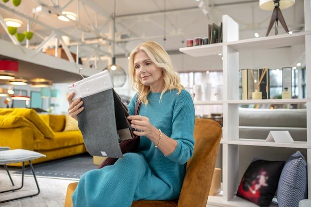 Wybór koloru. kobieta z próbkami materiału w dłoniach, siedząca w nowym fotelu w salonie meblowym, uważna szuka wyboru.
