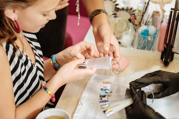 Wybór koloru. śliczna stylowa nastolatka czuje się niezwykle wesoła i podekscytowana przy wyborze koloru paznokci