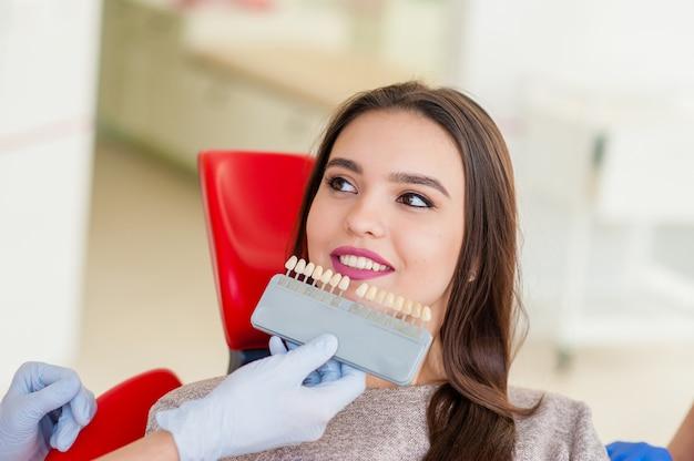 Wybór koloru zębów dla pięknej dziewczyny w stomatologii.