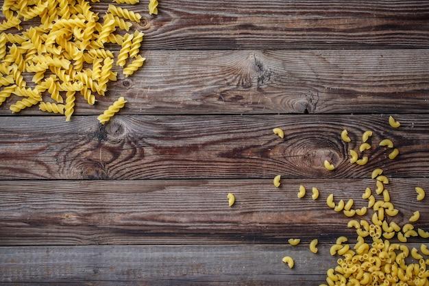 Wybór mieszanych makaronów suszonych na drewniane tła. płaski widok z góry z copyspace na tekst, logo lub inne.
