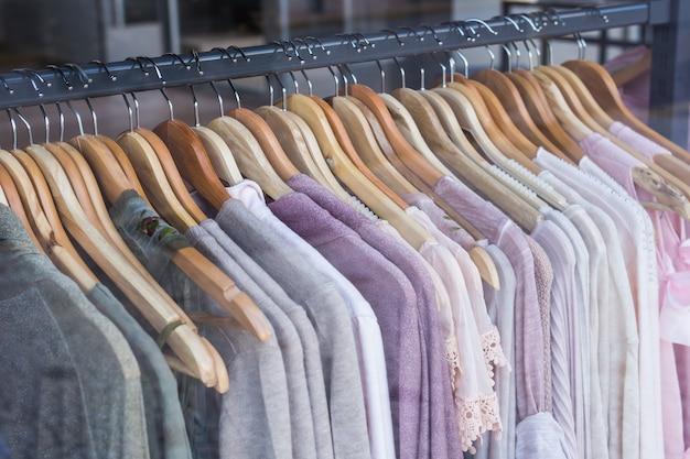 Wybór modnych ubrań w różnych kolorach na drewnianych wieszakach.