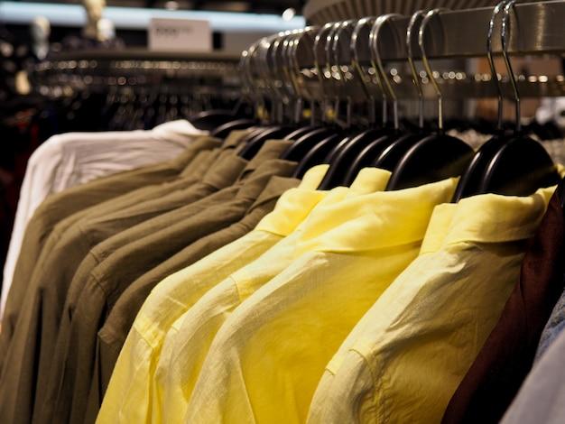 Wybór modnych ubrań w różnych kolorach na drewnianych wieszakach