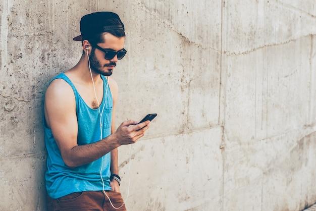 Wybór odpowiedniej listy odtwarzania. przystojny młody mężczyzna w słuchawkach, trzymający inteligentny telefon i patrzący na niego, stojąc na zewnątrz i opierając się o betonową ścianę