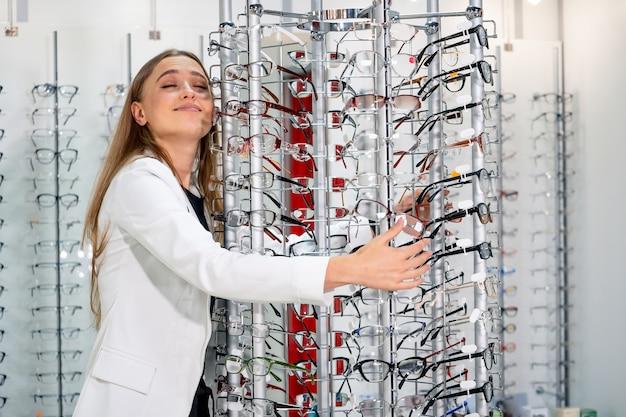Wybór okularów. klient w optyce. selektywne skupienie. kobieta patrząc do kamery. stań z okularami. szeroki asortyment w sklepie.