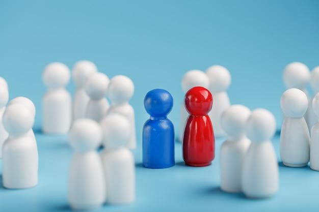 Wybór partnera seksualnego z miłości, relacje z tłumu monotonnych ludzi. czerwona kobieta i niebieski mężczyzna w tłumie białych ludzi.