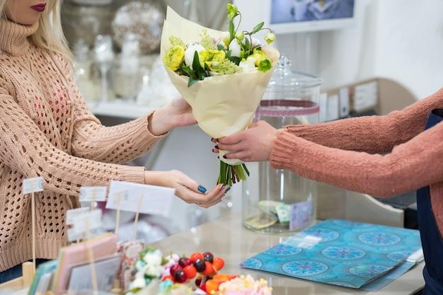 Wybór pięknego bukietu na specjalną okazję - urodziny, dzień matki lub kobiet, rocznicę. kobieta kupująca bukiet kwiatów w sklepie