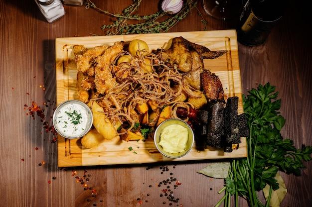 Wybór piwa i przekąsek. frytki, ryby, kiełbaski piwne na stole. widok z góry