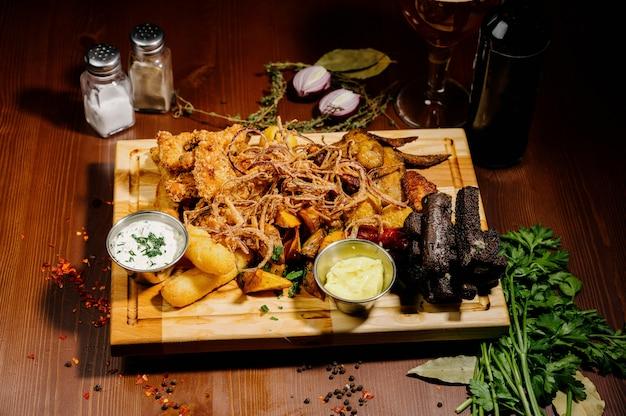 Wybór piwa i przekąsek. frytki, ryby, kiełbaski piwne na stole