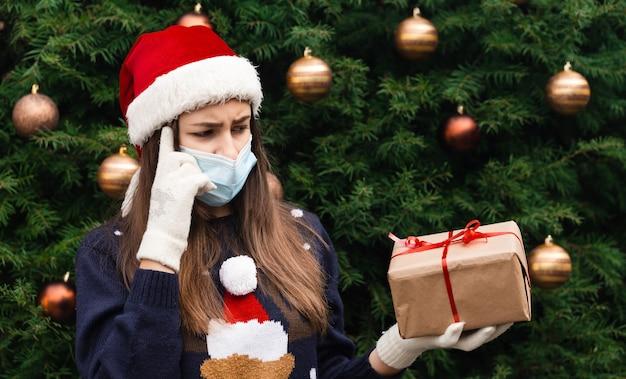 Wybór prezentu. gratulacje dla maski bożonarodzeniowej. portret kobiety w kapeluszu santa i białym swetrze w masce medycznej, dając prezent pudełko z czerwoną wstążką, bokeh choinkowe na tle