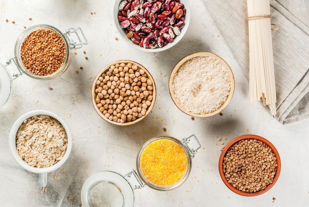 Wybór produktów bezglutenowych, zbóż: guma ksantanowa. kasza gryczana, ryż, makaron ryżowy, ciecierzyca, soczewica, kukurydza, fasola, płatki owsiane. w miseczkach i słoikach widok z góry na białym blacie kopia przestrzeń