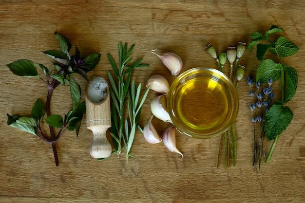 Wybór przypraw, ziół i zieleni. oliwa z oliwek, czosnek, pieprz, sól i rozmaryn. składniki do gotowania.