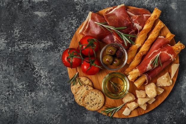 Wybór przystawek serowych i mięsnych z szynką prosciutto, parmezanem, paluszkami chlebowymi