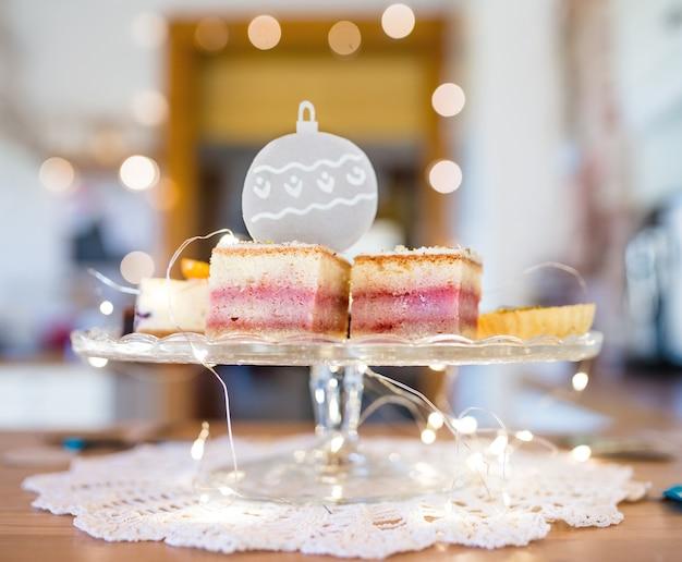 Wybór pysznych deserów tortowych na tacy, dekoracje świetlne.