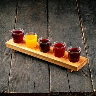 Wybór różnych naturalnych alkoholowych nalewek owocowych na czarnej drewnianej powierzchni