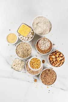 Wybór różnych rodzajów ziaren zbóż, kaszy w różnych miskach na tle białego marmuru, powyżej