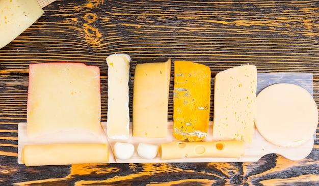 Wybór różnych serów na bufecie starannie ułożonych na drewnianej desce z twardym, półtwardym, miękkim, mozzarellą i serem z koziego mleka