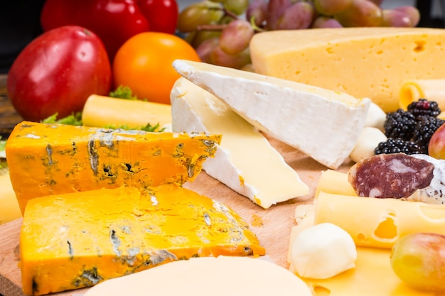 Wybór różnych serów na półmisku ze świeżymi składnikami sałatek i kiścią winogron z tyłu, gotowy do przygotowania i ułożenia na stole w formie bufetu