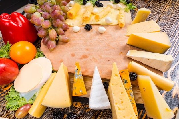 Wybór różnych serów ułożonych wokół drewnianej deski serów ze świeżymi winogronami, pomidorem, oliwkami i słodką papryką