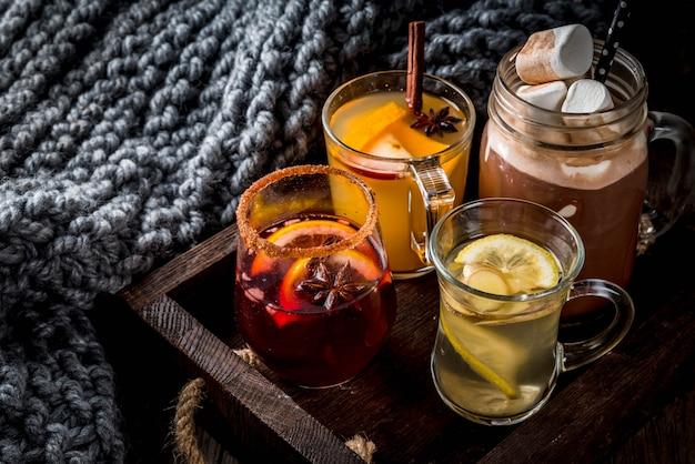 Wybór różnych tradycyjnych jesiennych napojów: gorąca czekolada z pianką, herbata z cytryną i imbirem, pikantna sangria z białej dyni, grzane wino. na drewnianym wieśniaka stole, kopii przestrzeń, selekcyjna ostrość