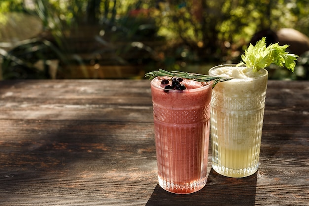 Wybór różowych koktajli jagodowych i koktajli mlecznych, podłoże drewniane