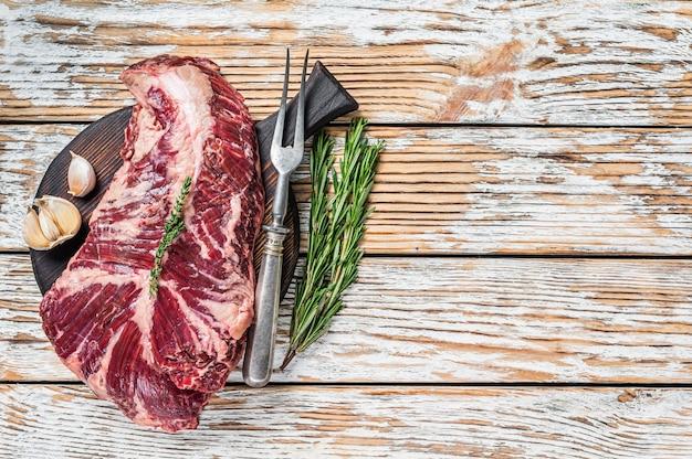 Wybór rzeźnika stek onglet wiszący delikatne mięso wołowe na desce do krojenia. białe drewniane tło. widok z góry. skopiuj miejsce.