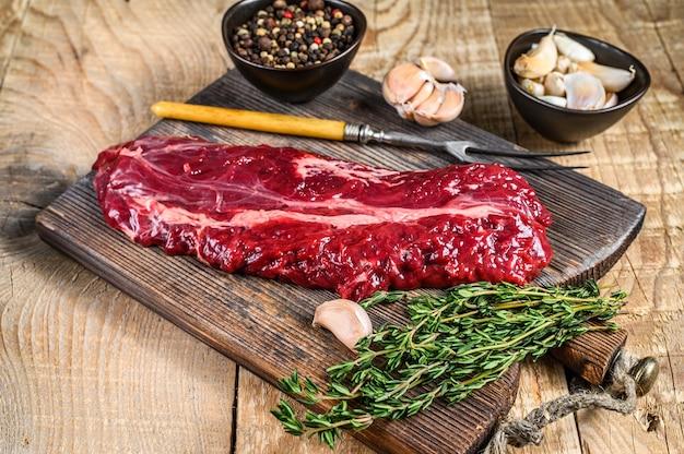 Wybór rzeźnika stek wiszący onglet delikatne mięso wołowe. drewniane tła. widok z góry.