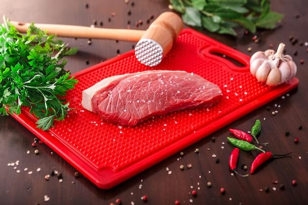 Wybór surowego mięsa na drewnianą deską do krojenia