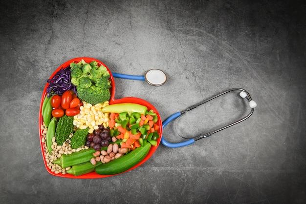 Wybór zdrowej żywności czyste jedzenie dla życia serca cholesterol dieta zdrowie świeże sałatki owocowe i zielone warzywa mieszane różne ziarna fasoli ziarno orzechów na czerwonym talerzu serca dla zdrowej żywności wegański kucharz