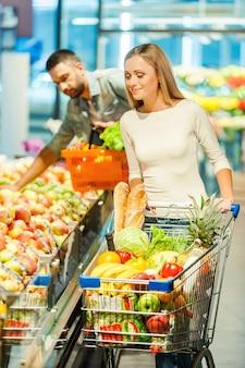Wybór zdrowej żywności. uśmiechnięta młoda kobieta trzymająca jabłko i patrząca w kamerę stojąc w sklepie spożywczym