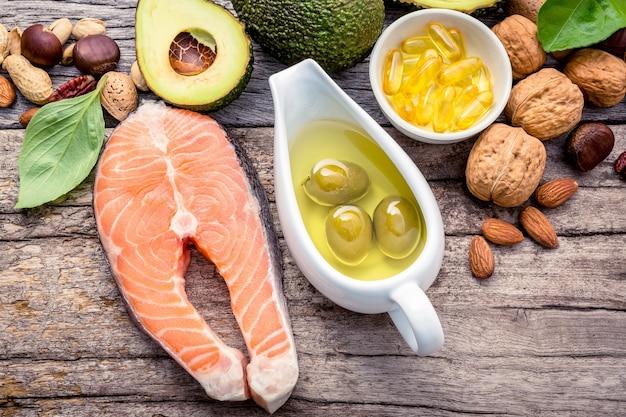 Wybór źródeł żywności omega 3 i nienasyconych tłuszczów na odrapanym drewnianym tle.